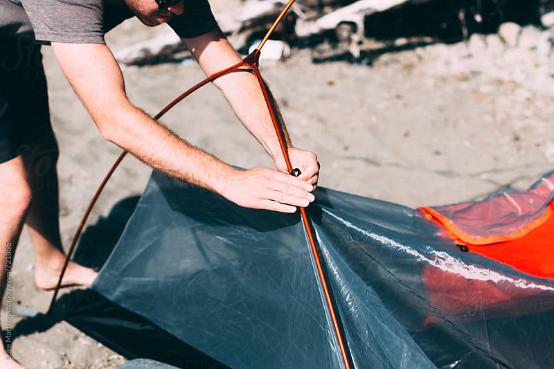 A Young Man Sets Up A Tent On The Sandy Beach by Luke Mattson for Stocksy United
