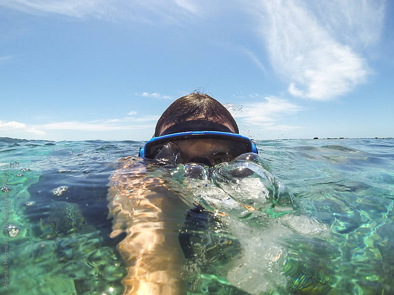 Man wearing diving mask snorkeling on the surface of tropical sea by Alejandro Moreno de Carlos for Stocksy United