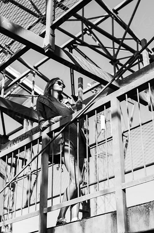 Sensual beautiful woman standing on metal platform. by Marko Milanovic for Stocksy United