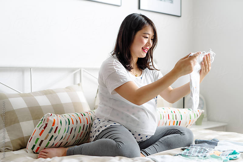 Pregnant woman looking at baby's clothes by MaaHoo Studio for Stocksy United