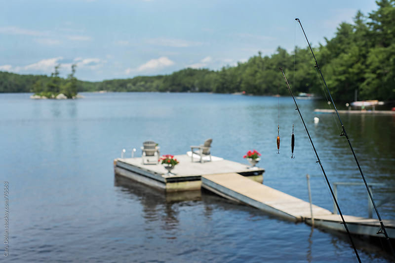 Two fishing poles rest near a dock on a lake by Cara Slifka for Stocksy United
