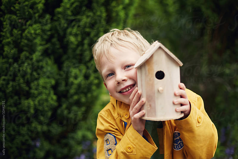 Child holding a birdhouse by sally anscombe for Stocksy United