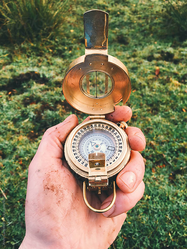 A close-up of a hand holding an old compass. by Andy Campbell for Stocksy United