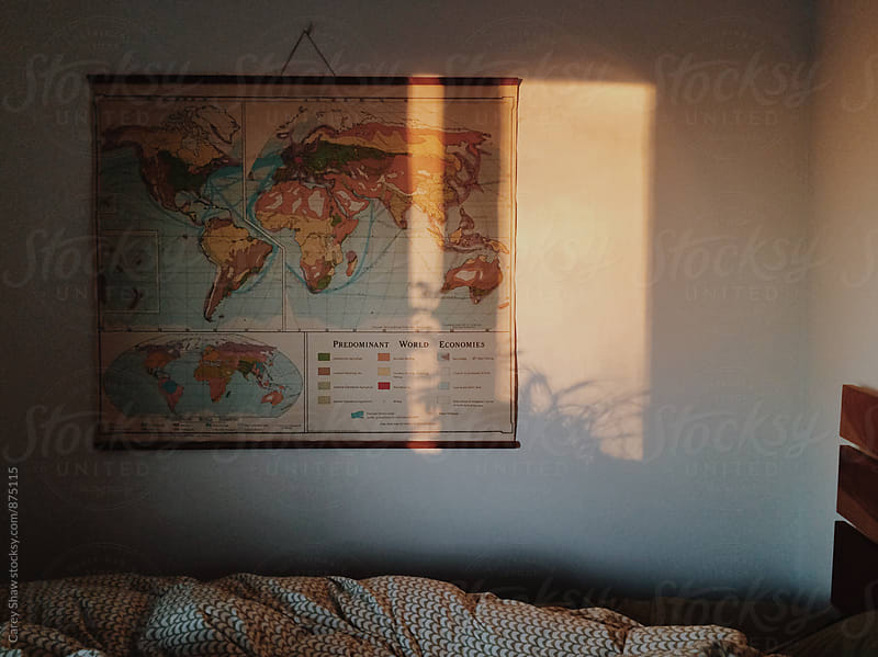 Dark bedroom with light reflecting on wall and map by Carey Shaw for Stocksy United