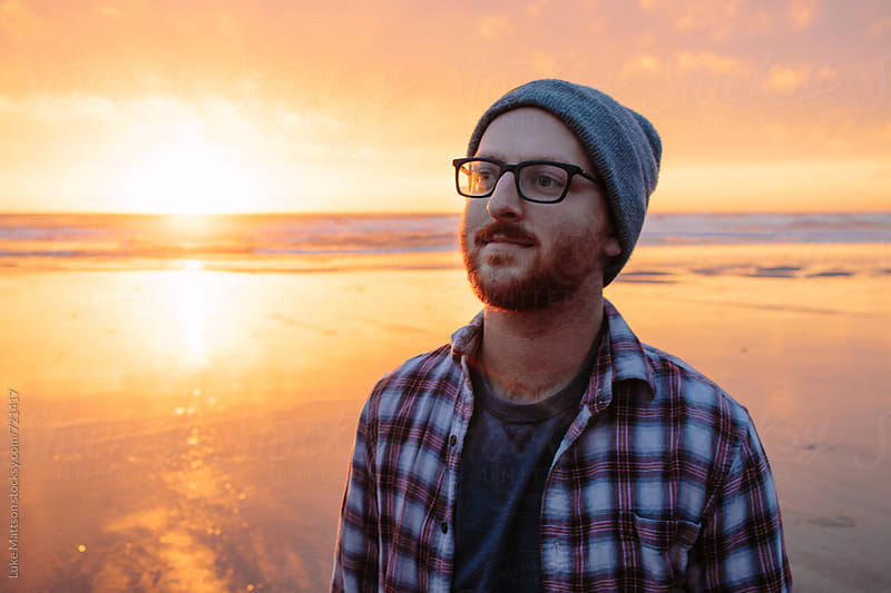 Content Young Man Wearing Glasses And Beanie Standing On Ocean Beach During Sunset by Luke Mattson for Stocksy United