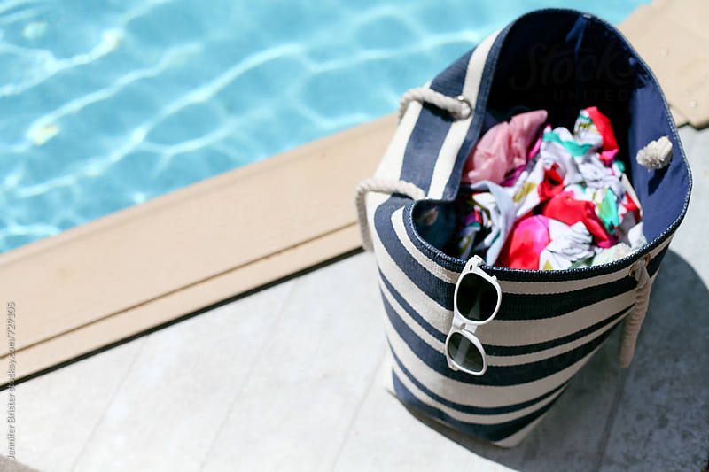 beach bag next to pool by Jen Brister for Stocksy United