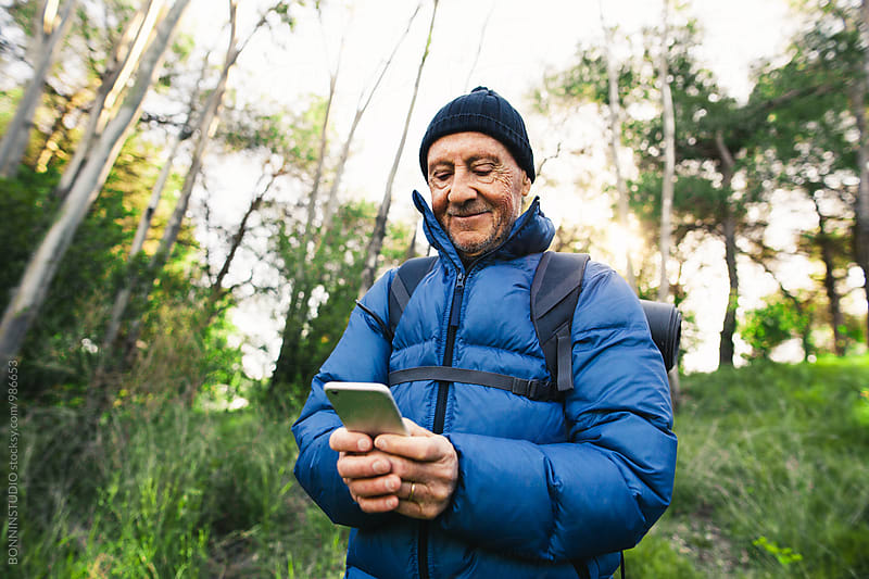 Portrait of a senior man using his phone in the woods.  by BONNINSTUDIO for Stocksy United