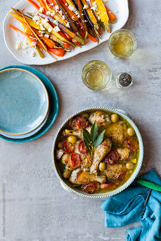 Chicken casserole with apricots, green olives and a side dish of roasted carrots by Nadine Greeff for Stocksy United