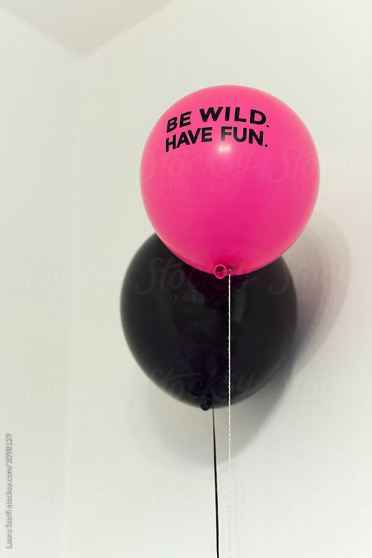 Two balloon with vibrant colors and the word Be wild have fun printed on one of them by Laura Stolfi for Stocksy United