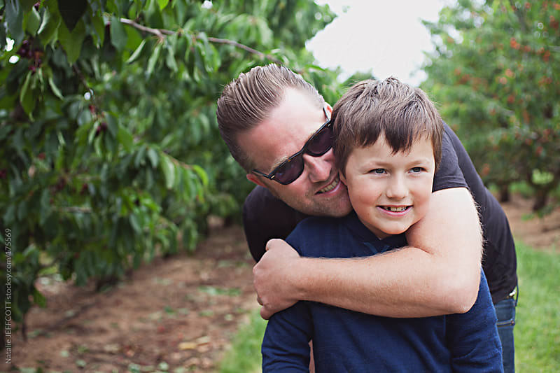 Father and son picking cherries from an orchard by Natalie JEFFCOTT for Stocksy United