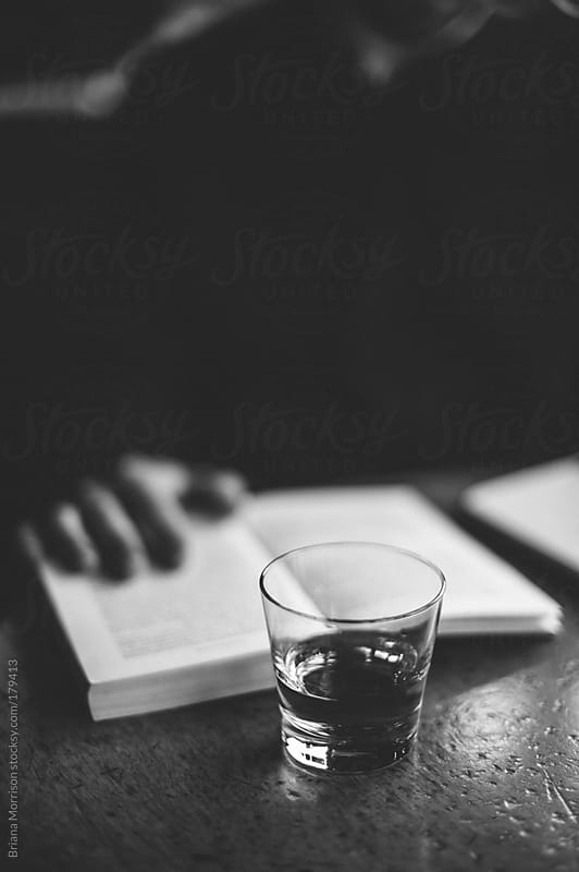 Glass of Scotch and Man Reading a Book by Briana Morrison for Stocksy United