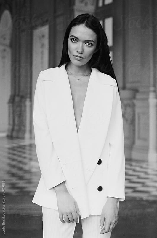 Woman wearing white suit looking at camera by Liubov Burakova for Stocksy United