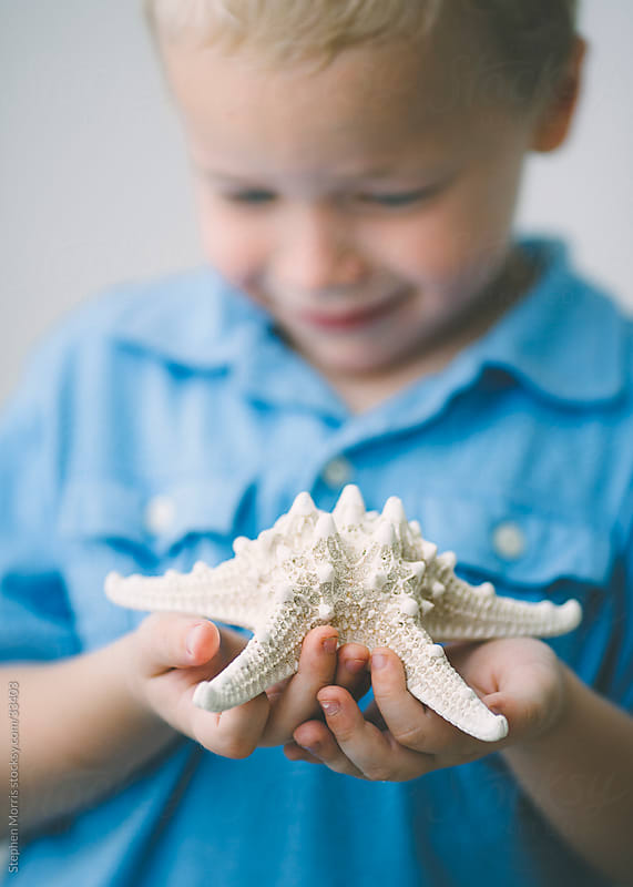 Boy Holding Starfish Close Up by Stephen Morris for Stocksy United
