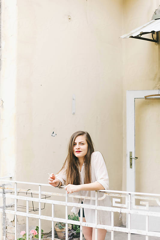 Young woman on the terrace by Marija Kovac for Stocksy United