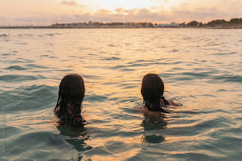 From behind: two people swimming on the sea by Lucas Ottone for Stocksy United