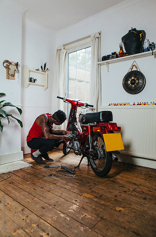 Cool tatooed man fixing his motorbike inside his house. by kkgas for Stocksy United