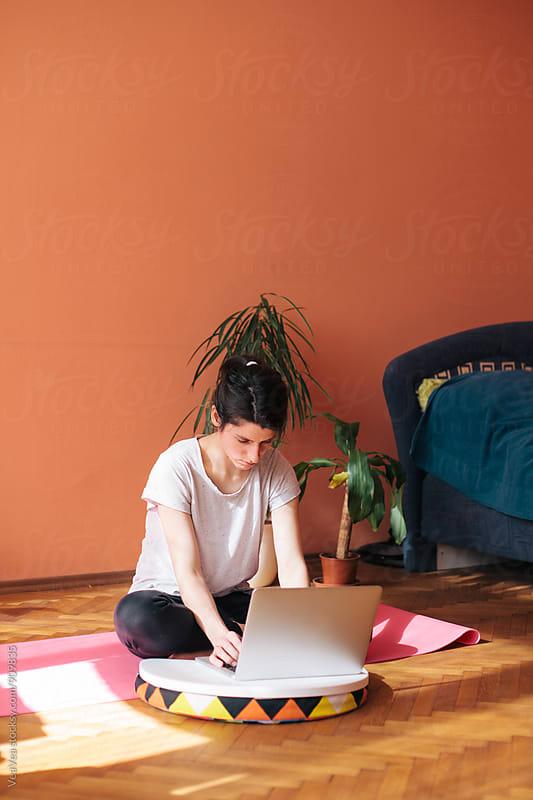 Woman having home yoga class by Marija Mandic for Stocksy United