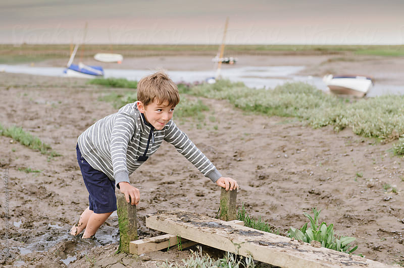 Cheeky child stuck in the mud by Rebecca Spencer for Stocksy United