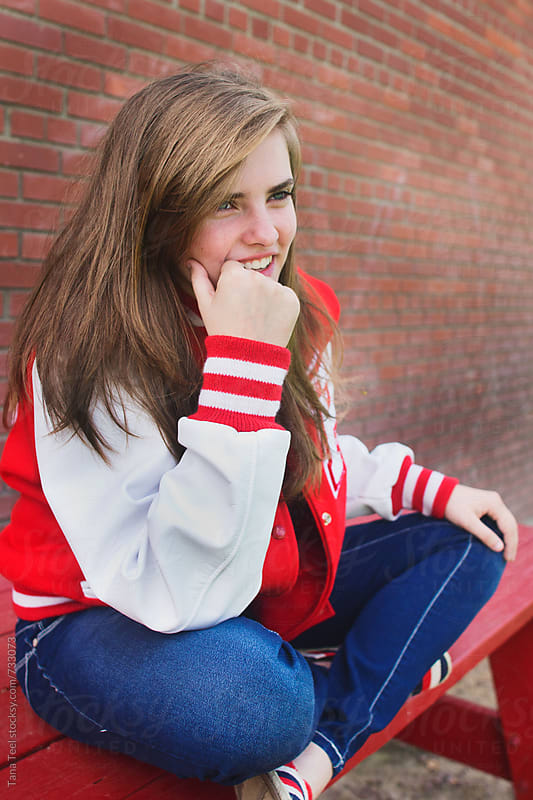 smiling teenage girl wearing letterman jacket sits crossed leg on picnic table by Tana Teel for Stocksy United