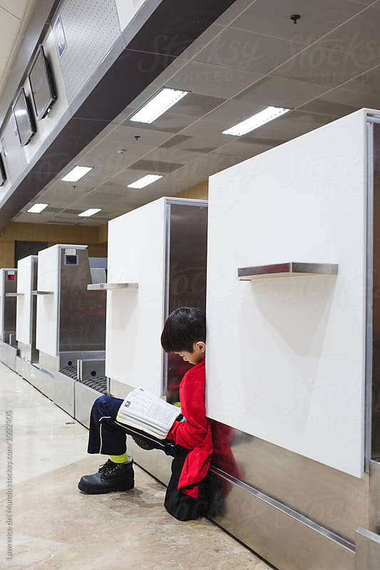 A young boy working on word puzzles at an empty check-in counter at the airport by Lawrence del Mundo for Stocksy United