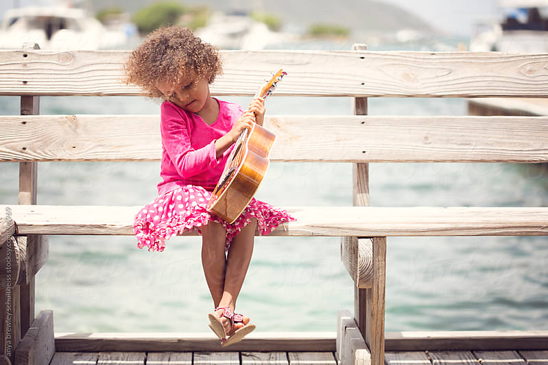 Young girl sitting on a bench playing her ukulele by anya brewley schultheiss for Stocksy United