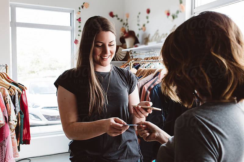 Young female entrepreneur using her phone to take a customer payment by Carey Shaw for Stocksy United