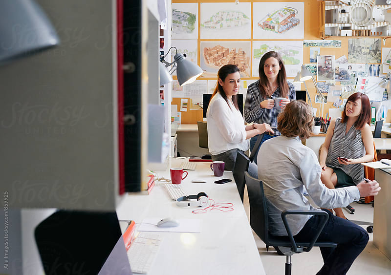 Group of architects having an informal meeting in busy office by Aila Images for Stocksy United