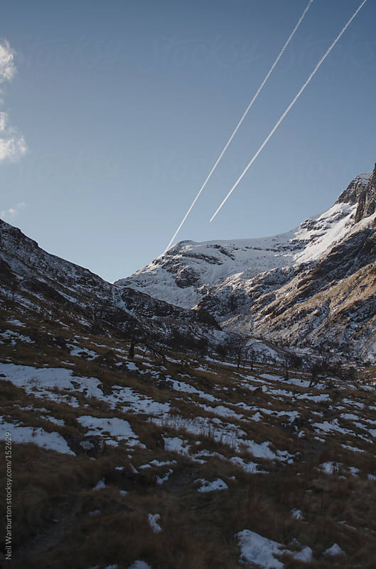 Plane Trails over Mountain Peak by Neil Warburton for Stocksy United