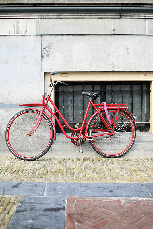 Red bicycle leaning against a wall by Marcel for Stocksy United