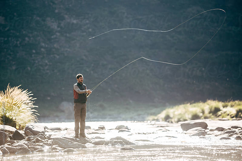 fly fisherman casting into a mountain river at dawn by Micky Wiswedel for Stocksy United