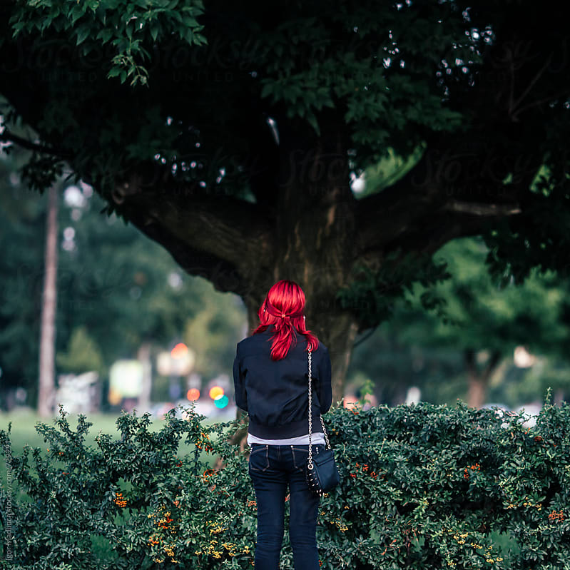 fashionable red-haired girl in front of a large tree in the park by Igor Madjinca for Stocksy United