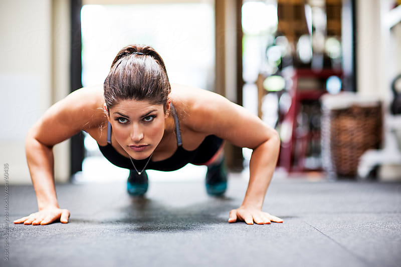 Woman working out by doing push up in the gym by Suprijono Suharjoto for Stocksy United
