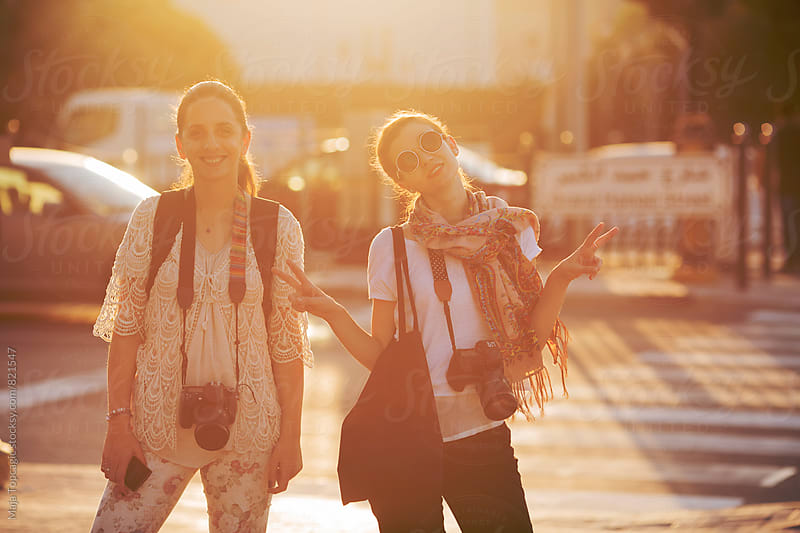 Two young female photographers smiling outdoors by Maja Topcagic for Stocksy United
