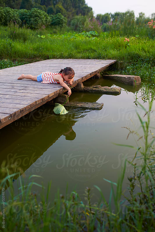 little girl lie on the wooden bridge outdoor by cuiyan Liu for Stocksy United
