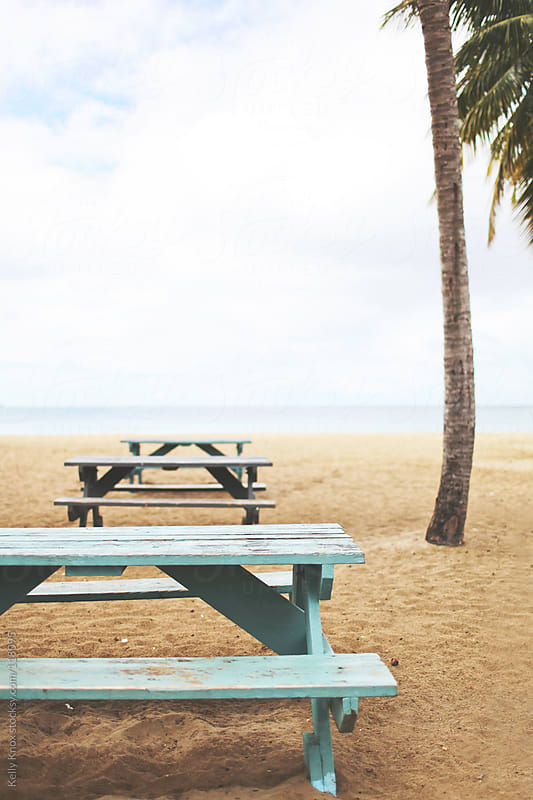 picnic tables on a beach by Kelly Knox for Stocksy United