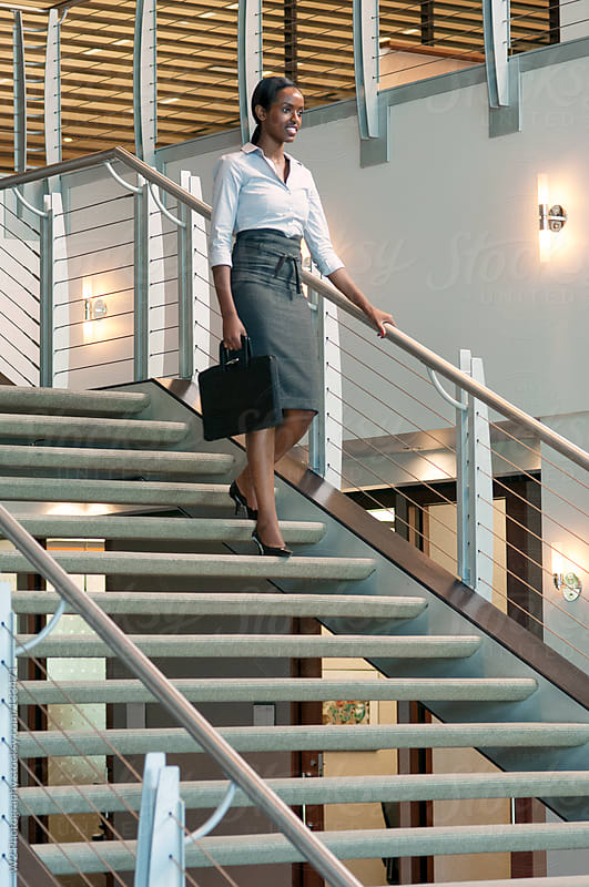 Executive businesswoman walking down a lobby staircase by W2 Photography for Stocksy United