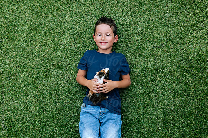 Cute Kid Playing with a Guinea Pig Lying on Grass by Victor Torres for Stocksy United