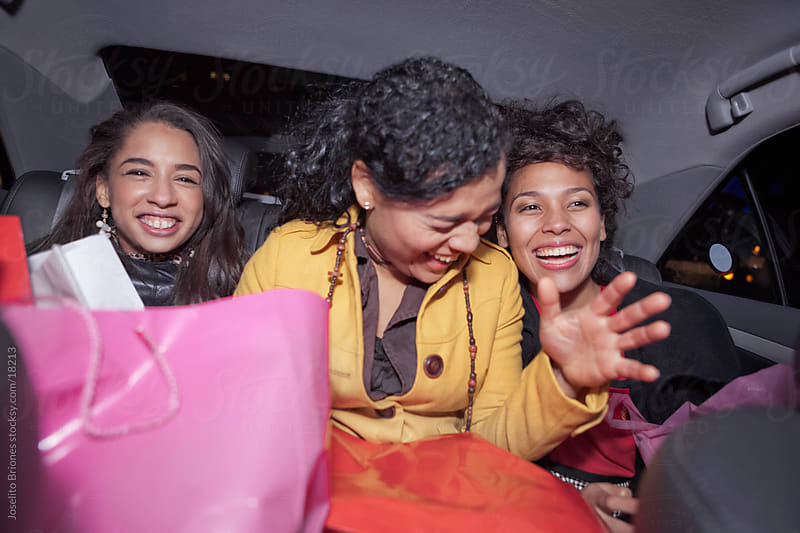 Hispanic/Latin-American Women Having a Laugh in the back of a New York Taxi by Joselito Briones for Stocksy United