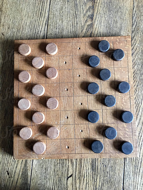 Old Checkers board on a wooden table ready for play, by Paul Phillips for Stocksy United