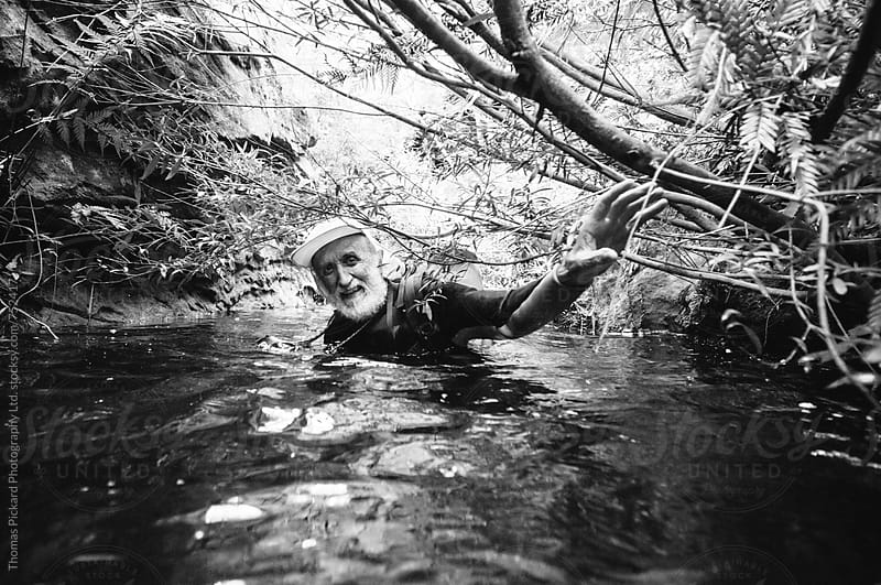 Senior man wading through deep water in a canyon. by Thomas Pickard Photography Ltd. for Stocksy United