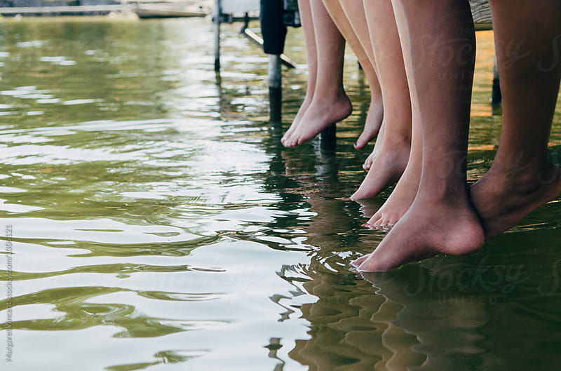 a group of teenagers sitting on a dock, tangle of legs by Margaret Vincent for Stocksy United