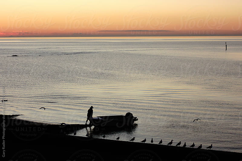 Man Launching Small Boat at Mornington, Victoria, Australia by Gary Radler Photography for Stocksy United