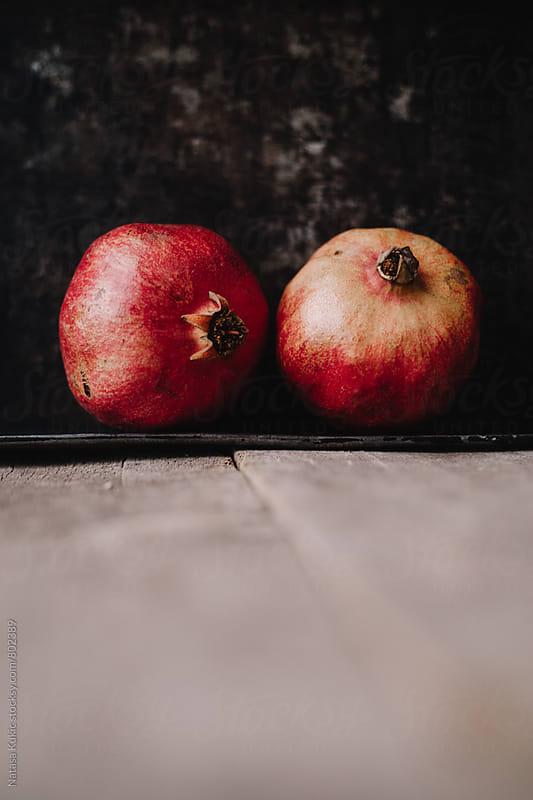 Pomegranates on a wooden background by Natasa Kukic for Stocksy United