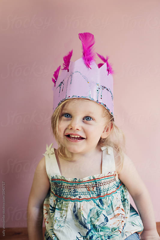 Happy smiling little girl wearing a homemade crown by sally anscombe for Stocksy United