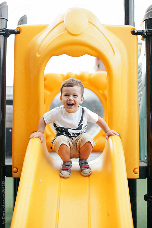 Happy kid playing on the slide. by Ani Dimi for Stocksy United