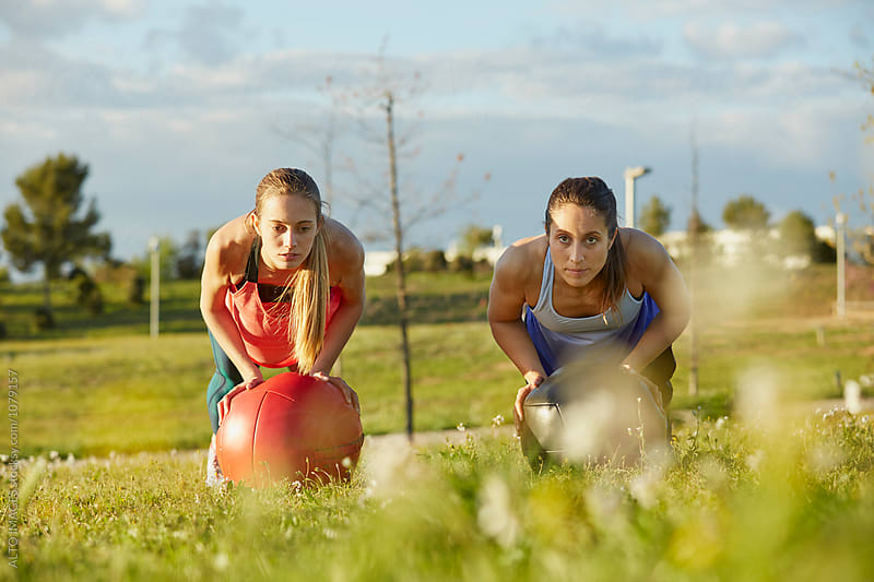 Sporty Women Doing Pushups With Medicine Balls In Park by ALTO IMAGES for Stocksy United