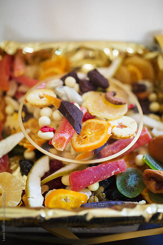 High angle view of candied fruit and chocolates on tray and on a dish by Laura Stolfi for Stocksy United