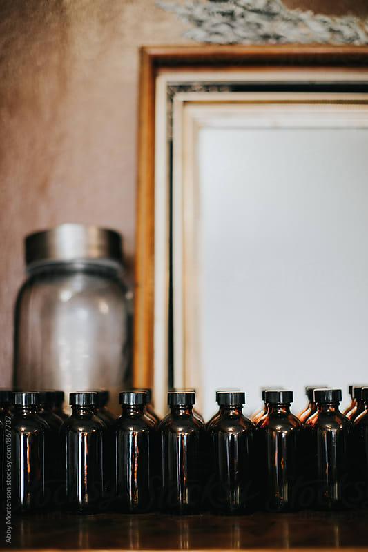 Little Brown Glass Bottles  by Abby Mortenson for Stocksy United