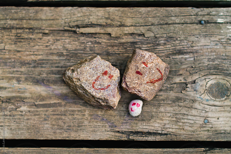 rocks with hand drawn happy faces by Jess Lewis for Stocksy United
