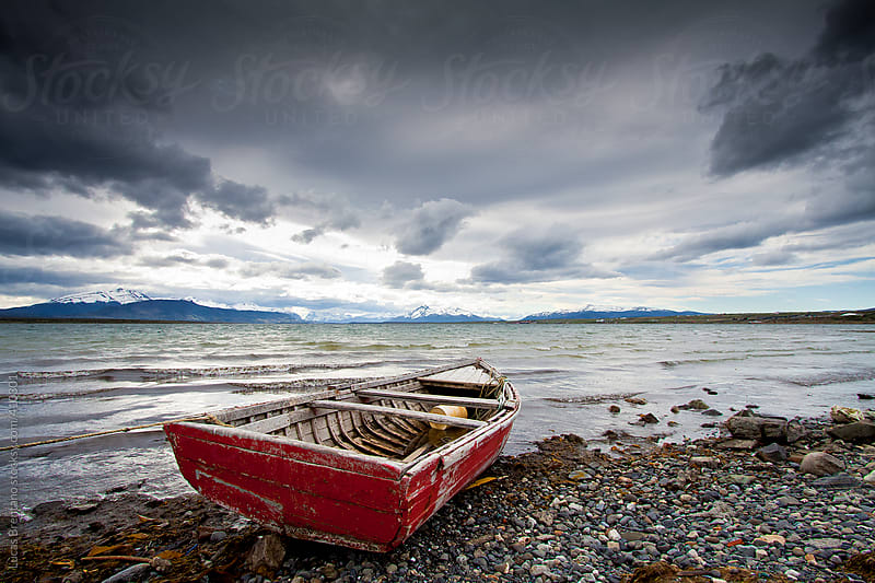 Abandoned boat on shore by Lucas Brentano for Stocksy United